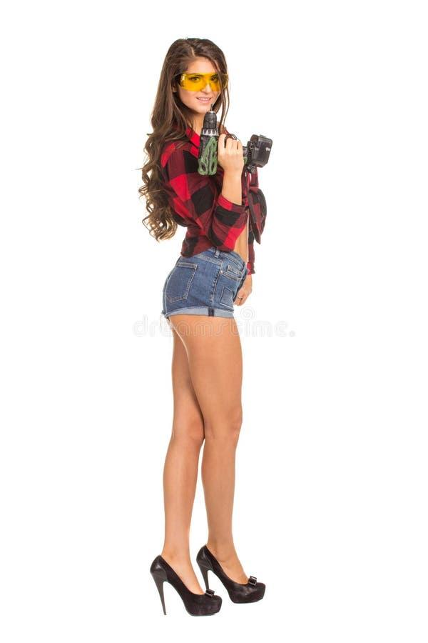 Mujer atractiva joven que celebra un taladro de la construcción fotografía de archivo libre de regalías