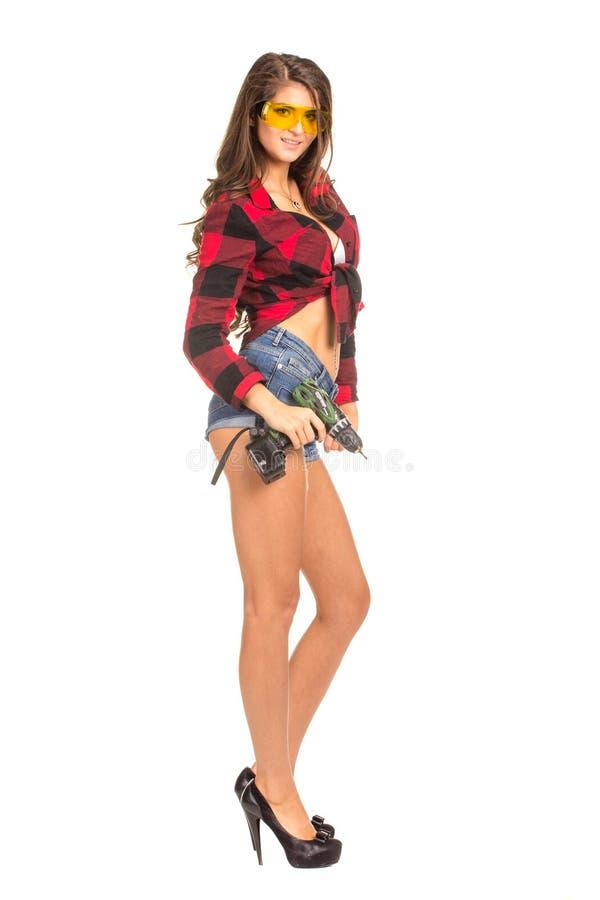 Mujer atractiva joven que celebra un taladro de la construcción imagenes de archivo