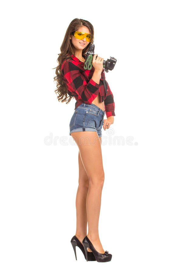 Mujer atractiva joven que celebra un taladro de la construcción fotos de archivo