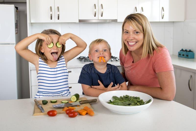 Mujer atractiva joven que cocina así como poco 3 y 7 años el jugar del hijo y de la hija feliz con la barra del pepino como obser imagen de archivo libre de regalías