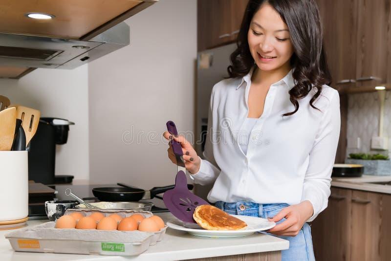 Mujer atractiva joven que cocina en nueva cocina foto de archivo