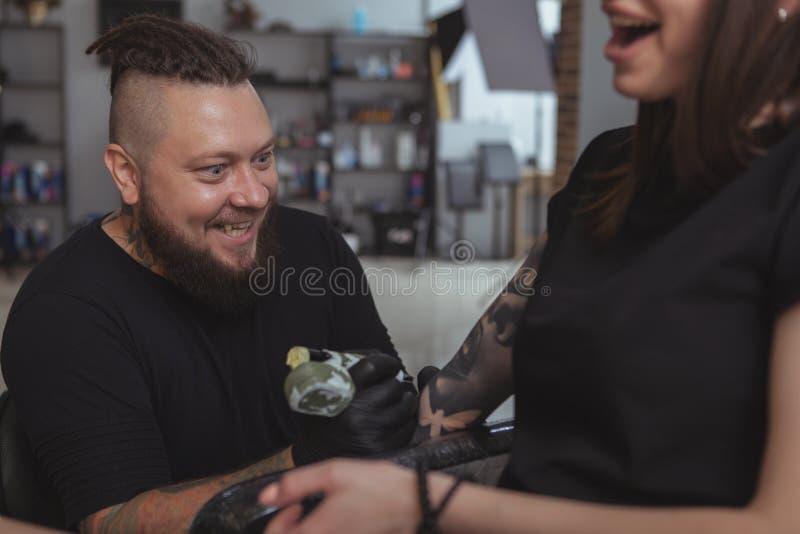 Mujer atractiva joven que consigue el nuevo tatuaje del tattooist profesional fotografía de archivo libre de regalías