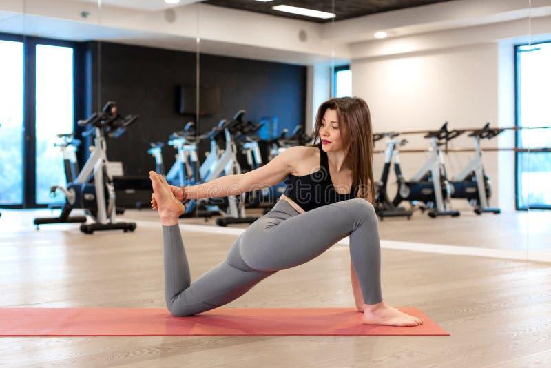 Mujer atractiva joven que hace estirando ejercicios en gimnasio imagenes de archivo