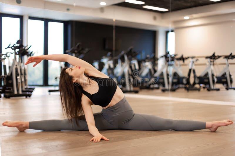 Mujer atractiva joven que hace estirando ejercicios en gimnasio fotografía de archivo