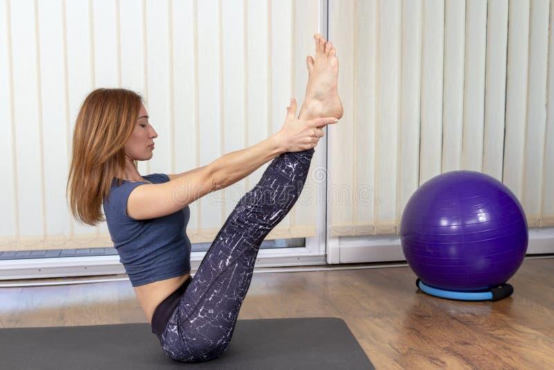 Mujer atractiva joven que hace los ejercicios de Pilates en casa fotografía de archivo libre de regalías