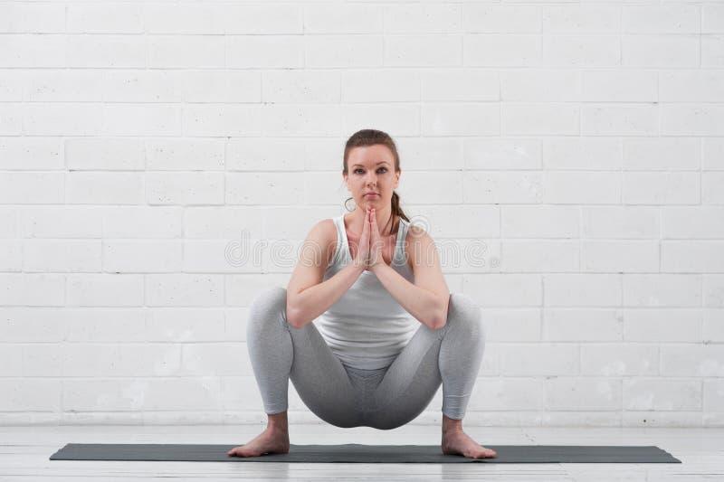Mujer atractiva joven que hace yoga dentro foto de archivo
