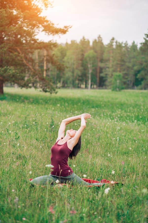 Mujer atractiva joven que hace yoga en el campo imagen de archivo libre de regalías