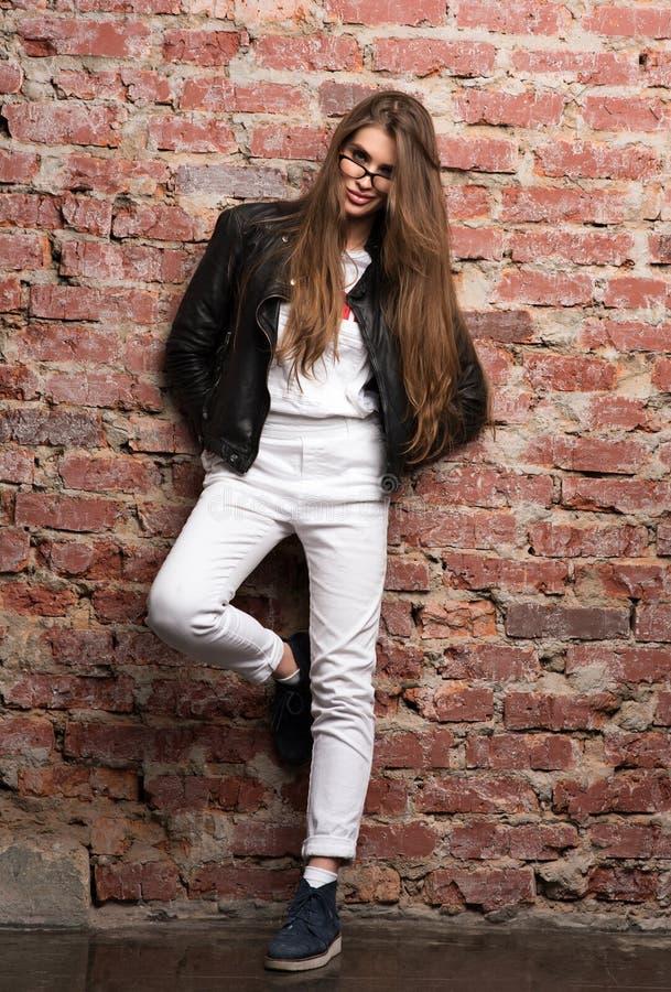 Mujer atractiva joven que presenta contra una pared de ladrillo Appearamce elegante, chaqueta de cuero negra fotos de archivo