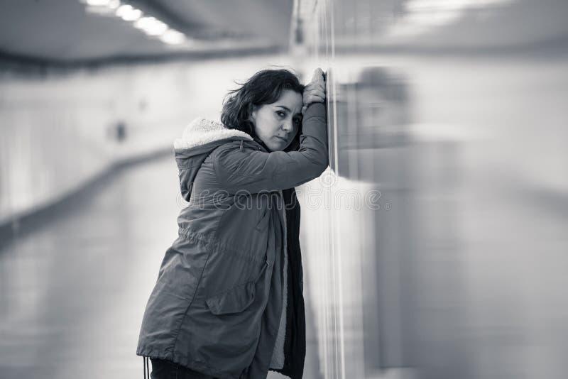 Mujer atractiva joven que se inclina en cansado triste de la sensaci?n de la pared del subterr?neo imágenes de archivo libres de regalías