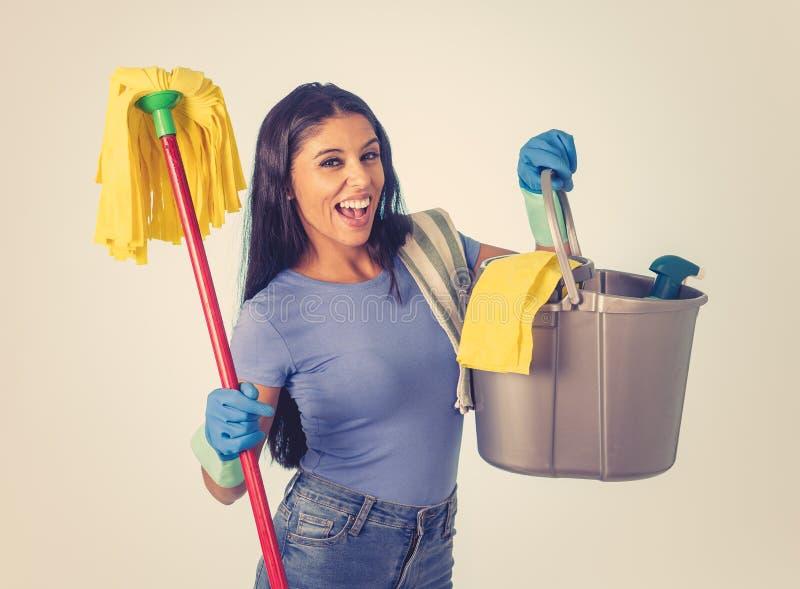 Mujer atractiva joven que sostiene las herramientas y los productos de la limpieza en el cubo aislado en fondo azul fotografía de archivo libre de regalías