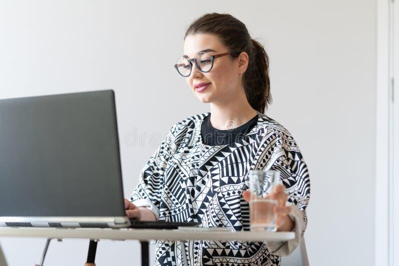 Mujer atractiva joven que trabaja en el ordenador port?til en apartamentos brillantes modernos imagenes de archivo