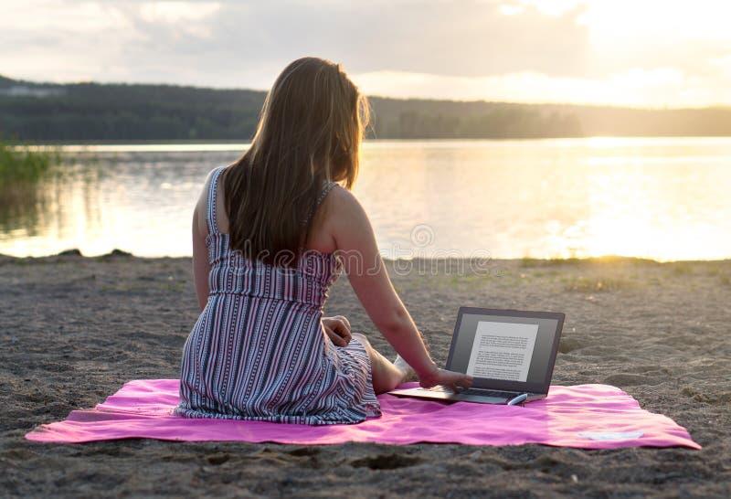Mujer atractiva joven que usa el ordenador portátil en la playa en la puesta del sol foto de archivo libre de regalías