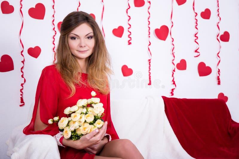 Mujer atractiva magnífica en la sentada roja en el sofá con las flores en la decoración fotografía de archivo