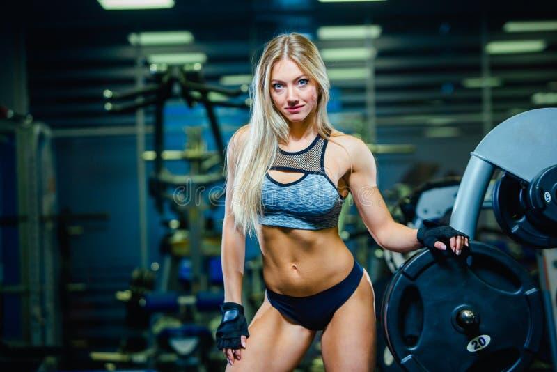 Mujer atractiva muscular de la mujer de la aptitud que se relaja en el gimnasio Concepto de forma de vida sana Bodybuilder en la  foto de archivo libre de regalías