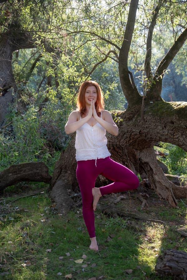 Mujer atractiva pelirroja preciosa joven del jengibre que hace ejercicios de la yoga con las manos para arriba en una pierna en n imagen de archivo