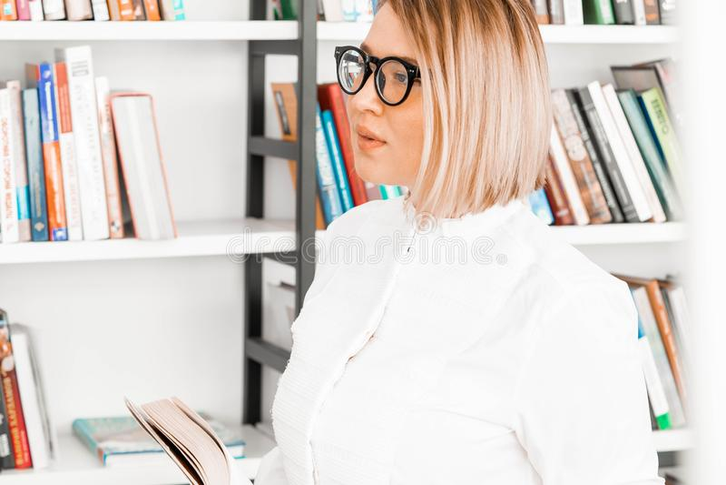Mujer atractiva pensativa joven en ropa formal que lee un libro en la biblioteca fotografía de archivo