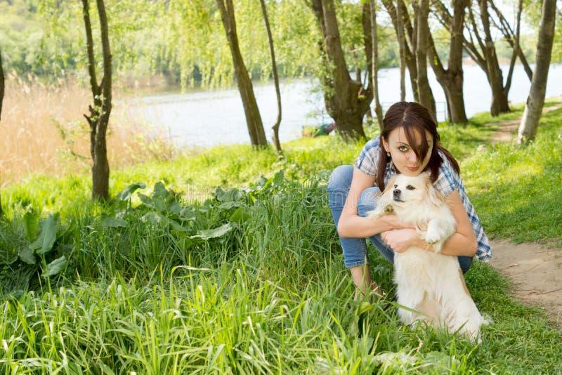 Mujer atractiva que abraza su perro minúsculo foto de archivo libre de regalías