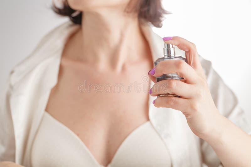 Mujer atractiva que aplica perfume fotografía de archivo