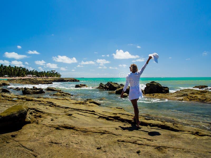 Mujer atractiva que camina a lo largo de la opinión de la playa sobre un día de verano fotografía de archivo