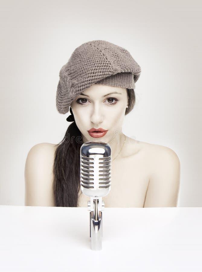 Mujer atractiva que canta en el mic retro foto de archivo