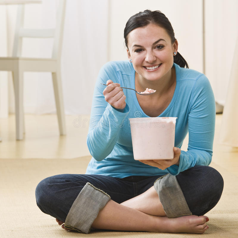 Mujer atractiva que come el helado foto de archivo libre de regalías