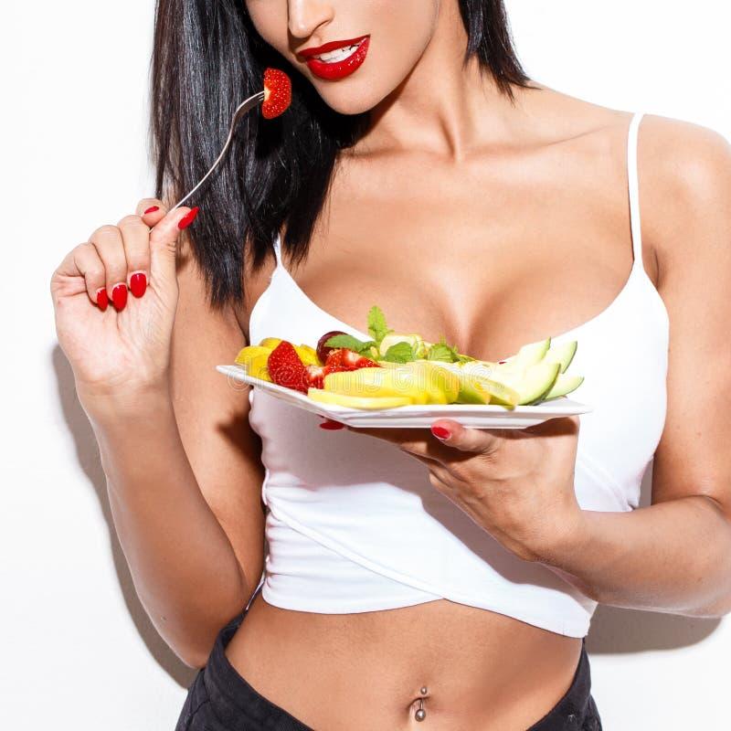 Mujer atractiva que come la ensalada de fruta imagen de archivo libre de regalías