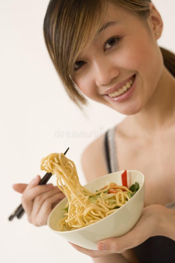 Mujer atractiva que come los tallarines imagenes de archivo