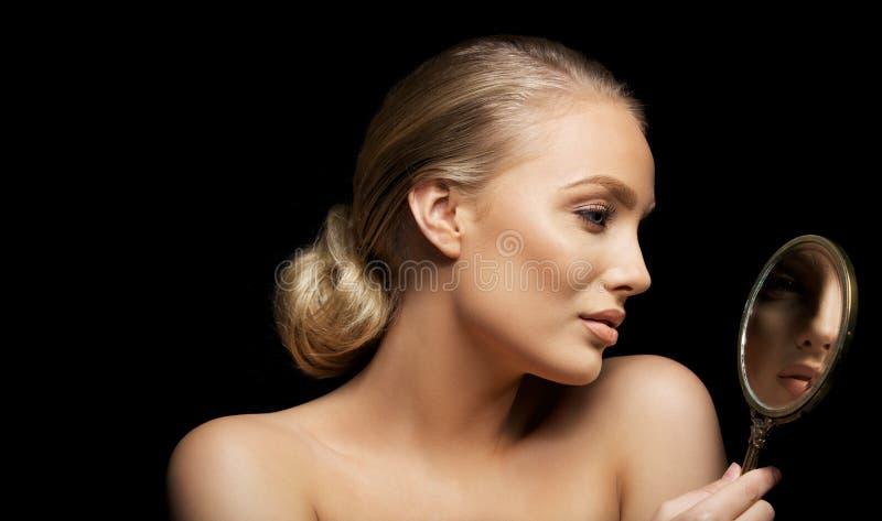 Mujer atractiva que comprueba su maquillaje imagenes de archivo