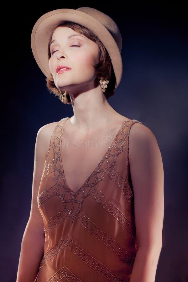 Mujer atractiva que desgasta el sombrero de fieltro beige en stlyle retro con cl fotos de archivo