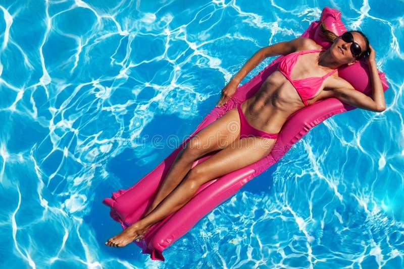 Mujer atractiva que disfruta de bronceado en el colchón de aire fotos de archivo