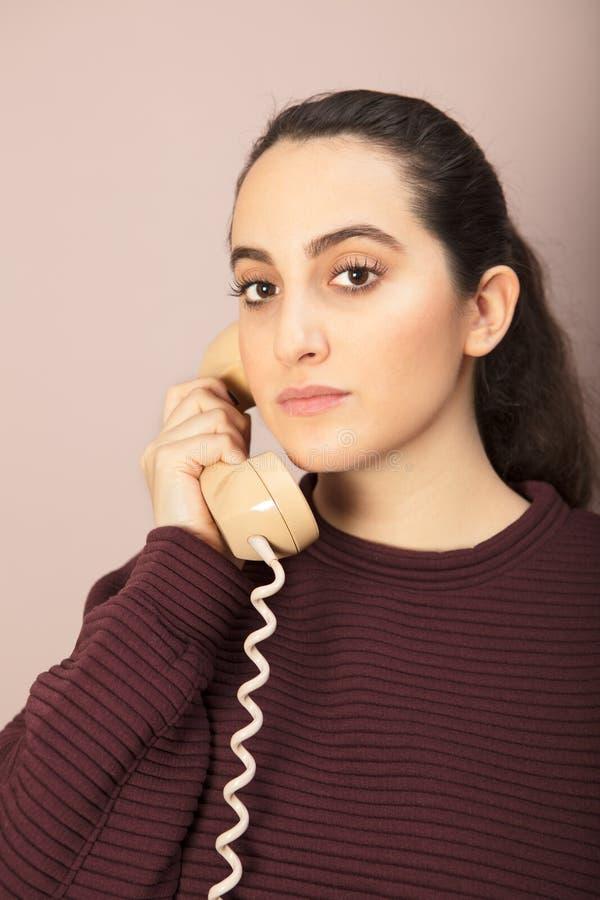 Mujer atractiva que escucha una conversación telefónica imagen de archivo