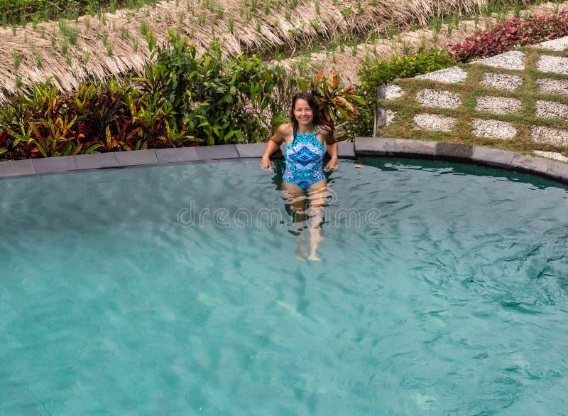 Mujer atractiva que goza del sol en la piscina del verano del infinito en el centro turístico lujoso fotografía de archivo