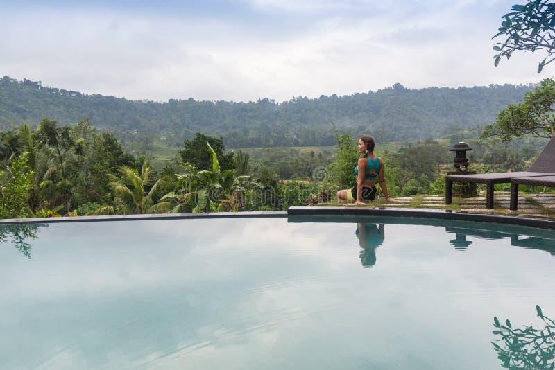 Mujer atractiva que goza del sol en la piscina del verano del infinito en el centro turístico lujoso imagen de archivo