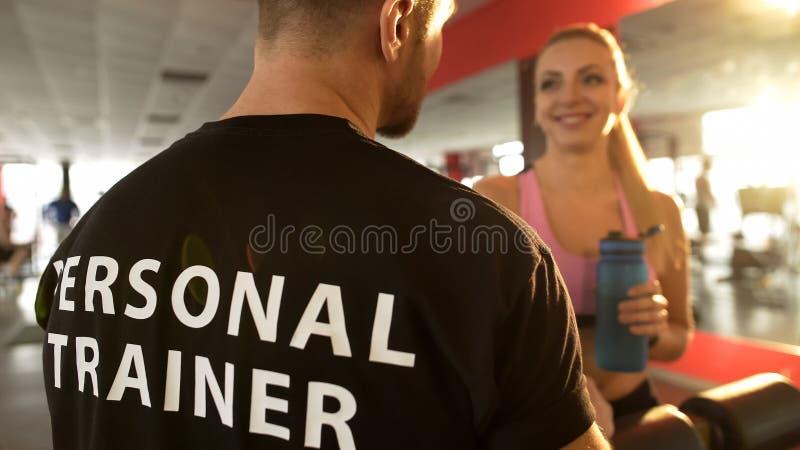 Mujer atractiva que habla con el instructor personal mientras que teniendo rotura después de ejercicios imagen de archivo libre de regalías