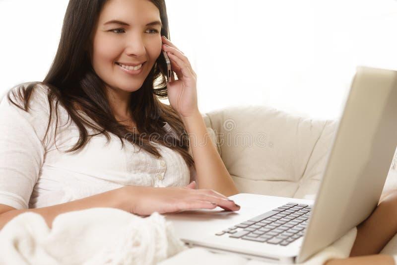Mujer atractiva que habla en el teléfono y que usa un ordenador portátil imagen de archivo