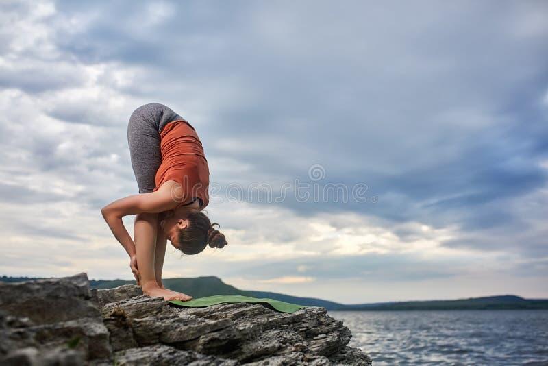 Mujer atractiva que hace ejercicio de la yoga en la piedra grande contra el río hermoso imagen de archivo