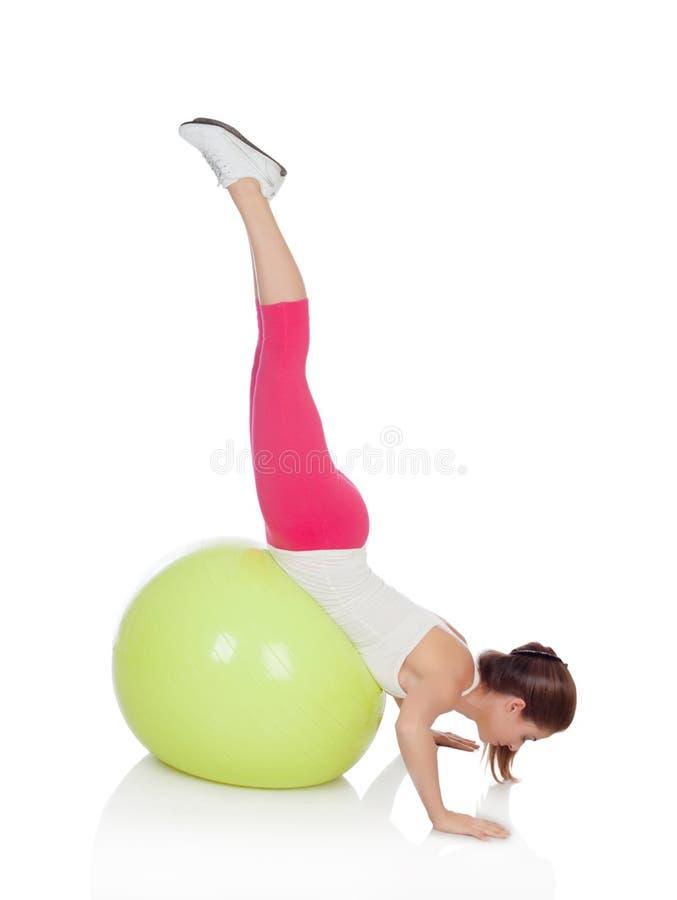 Mujer atractiva que hace pilates con una bola verde grande fotografía de archivo