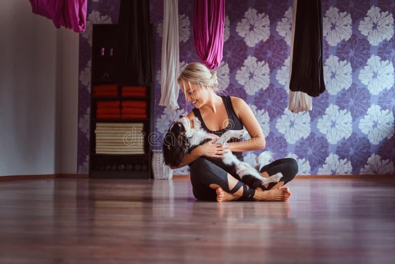 Mujer atractiva que juega con su perro lindo mientras que se sienta en piso en club de fitness de la yoga fotos de archivo