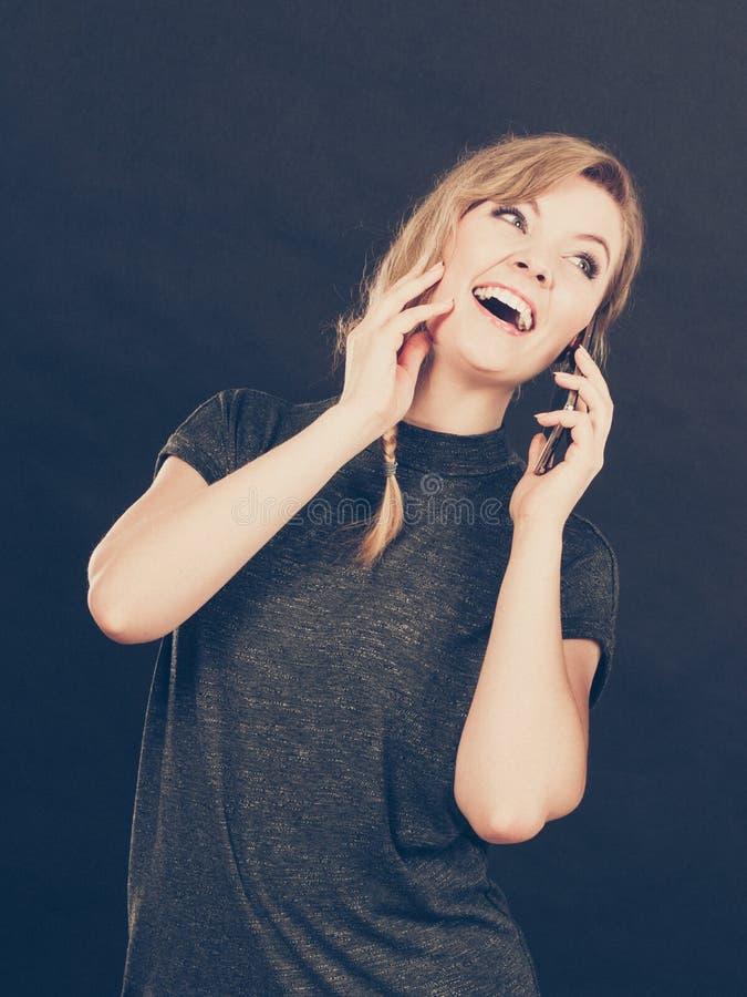 Mujer atractiva que liga mandar un SMS en el teléfono móvil fotos de archivo libres de regalías