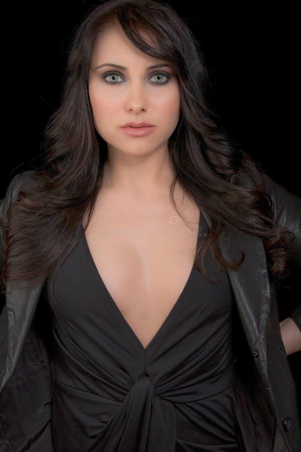 Mujer atractiva que lleva el vestido y la chaqueta negros imagen de archivo