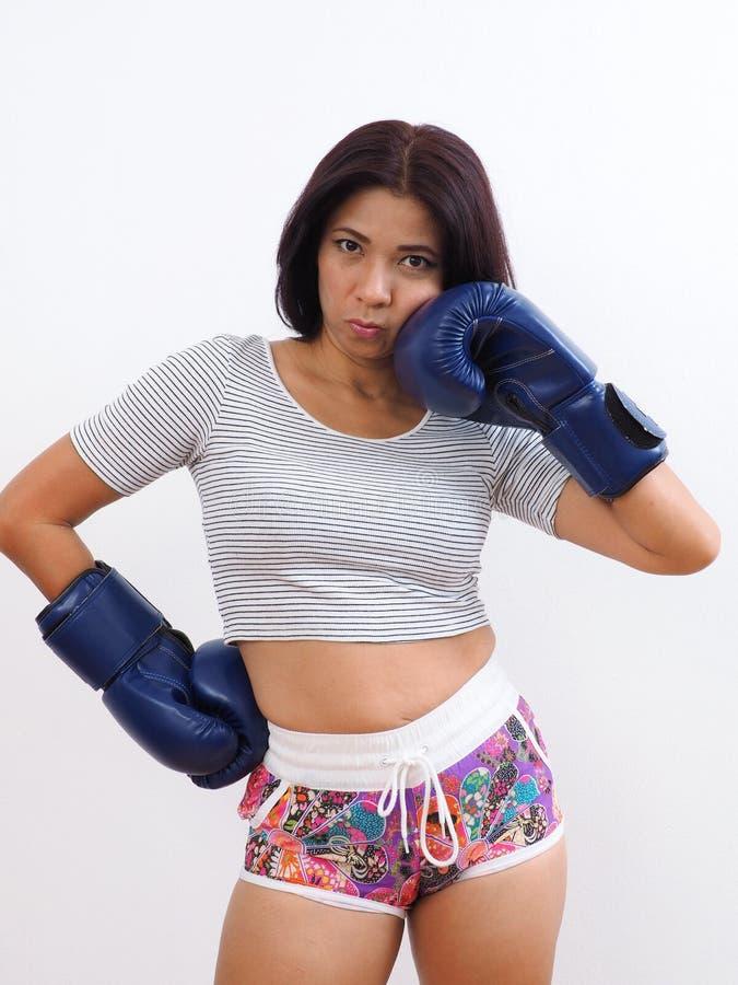 Mujer atractiva que lleva guantes de boxeo azules imagenes de archivo
