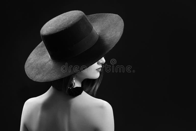 Mujer atractiva que lleva un sombrero que presenta en fondo negro fotos de archivo