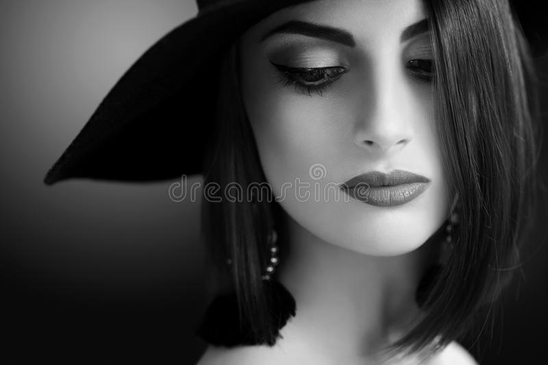 Mujer atractiva que lleva un sombrero que presenta en fondo negro imagen de archivo