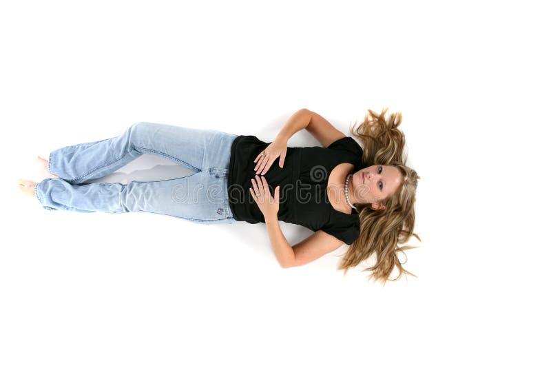 Mujer atractiva que miente en ella detrás con el pelo separado hacia fuera foto de archivo libre de regalías
