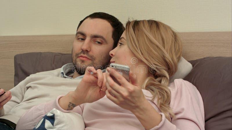 Mujer atractiva que miente en la cama que manda un SMS en el teléfono móvil que sonríe, mientras que su palanca del socio en la p foto de archivo