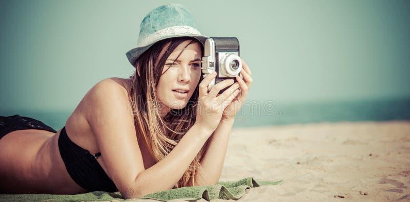 Mujer atractiva que miente en la playa que toma la foto con la cámara del vintage foto de archivo libre de regalías
