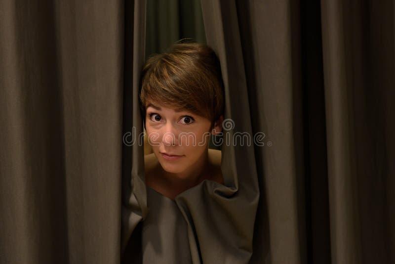 Mujer atractiva que mira a escondidas hacia fuera de las cortinas exhaustas fotografía de archivo libre de regalías