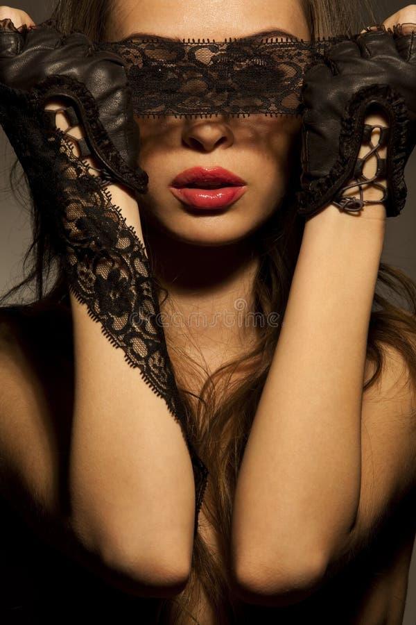 Mujer atractiva que mira a través de cordón a cielo abierto negro fotografía de archivo