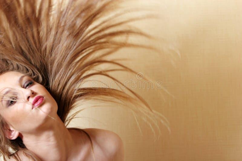 Mujer atractiva que mueve de un tirón el pelo imagen de archivo
