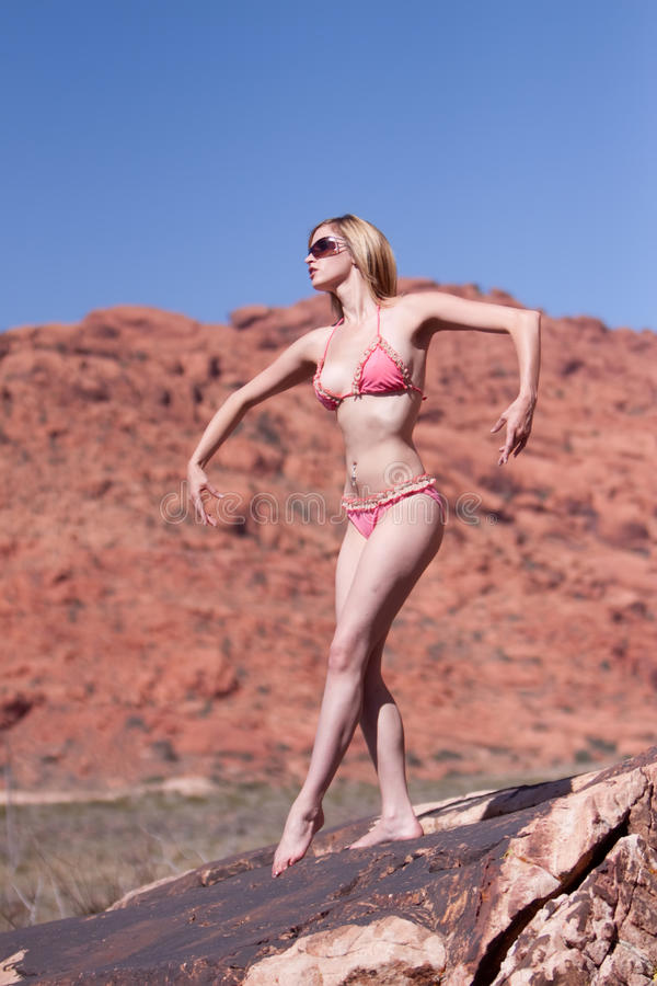 Mujer atractiva que presenta en rocas rojas foto de archivo